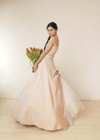 Ein modell im Brautkleid mit einm Tulpenstrauß in den Händen